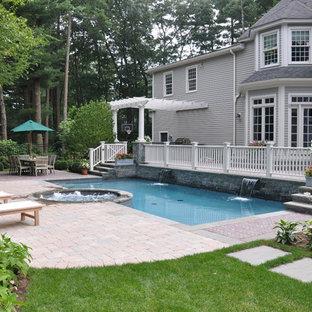 Diseño de piscinas y jacuzzis alargados, clásicos, de tamaño medio, rectangulares, en patio trasero, con adoquines de ladrillo