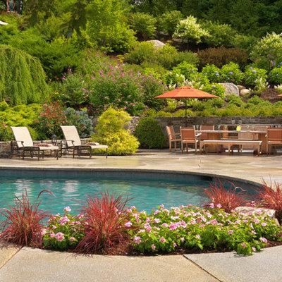 Large elegant backyard concrete paver and custom-shaped pool fountain photo in Boston