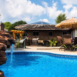 """Foto di una grande piscina monocorsia tropicale a """"C"""" dietro casa con fontane e piastrelle"""