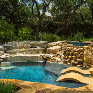 Hot tub - rustic stone and custom-shaped natural hot tub idea in Other