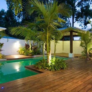 Immagine di una piscina tropicale di medie dimensioni e dietro casa con pedane