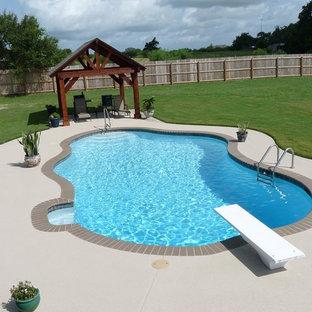 Imagen de piscina alargada, clásica, grande, a medida, en patio trasero, con granito descompuesto