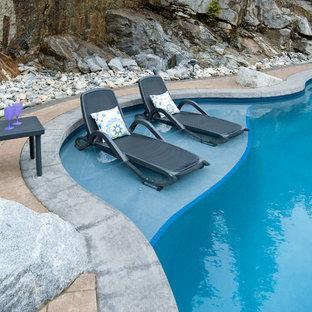 Imagen de piscina ecléctica, a medida, en patio trasero, con adoquines de ladrillo