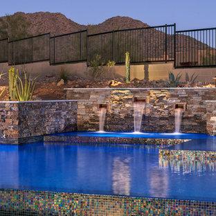 Imagen de piscina con fuente infinita, contemporánea, de tamaño medio, a medida, en patio trasero, con adoquines de piedra natural