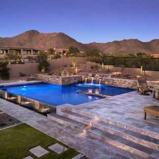 Пример оригинального дизайна интерьера: бассейн-инфинити среднего размера, произвольной формы на заднем дворе в стиле фьюжн с фонтаном и покрытием из каменной брусчатки