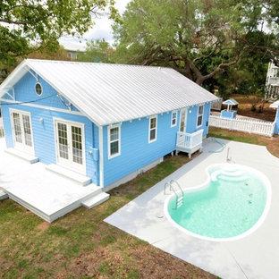 Diseño de piscina alargada, exótica, pequeña, tipo riñón, en patio trasero, con losas de hormigón