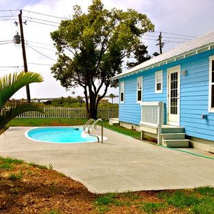 Diseño de piscina alargada, tropical, pequeña, tipo riñón, en patio trasero, con losas de hormigón