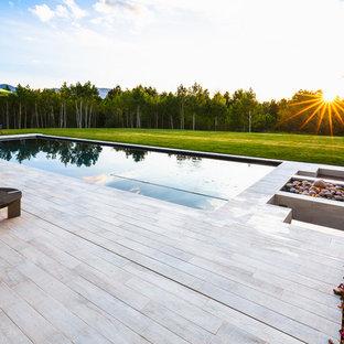 デンバーの中くらいの長方形コンテンポラリースタイルのおしゃれな裏庭プール (デッキ材舗装) の写真