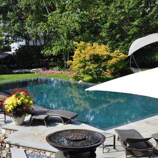 Foto de piscina infinita, nórdica, grande, rectangular, en patio trasero, con adoquines de piedra natural