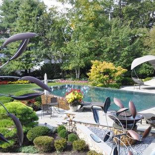 Ejemplo de piscina infinita, nórdica, grande, rectangular, en patio trasero, con adoquines de piedra natural