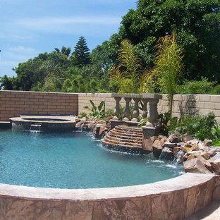 Diseño de piscinas y jacuzzis alargados, clásicos, de tamaño medio, tipo riñón, en patio trasero, con suelo de hormigón estampado