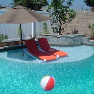 Modelo de piscinas y jacuzzis alargados, tradicionales, de tamaño medio, en patio trasero