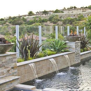 Diseño de piscina con fuente alargada, clásica, de tamaño medio, en forma de L, en patio trasero, con adoquines de piedra natural