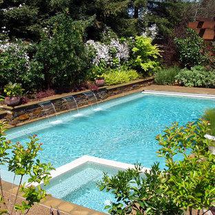 Foto de piscina con fuente alargada, contemporánea, grande, rectangular, en patio trasero, con granito descompuesto