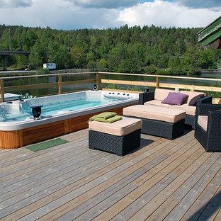 Immagine di una piscina fuori terra country rettangolare di medie dimensioni e dietro casa con una vasca idromassaggio e pedane