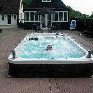 Foto di una piscina fuori terra classica rettangolare di medie dimensioni e dietro casa con una vasca idromassaggio e pedane