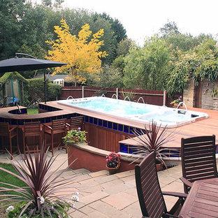 Immagine di una piscina minimalista rettangolare di medie dimensioni e dietro casa con una vasca idromassaggio e pedane
