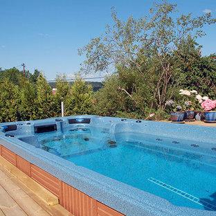 Modelo de piscinas y jacuzzis clásicos renovados, de tamaño medio, rectangulares, en patio trasero, con entablado