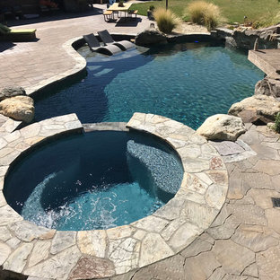 Large modern backyard custom-shaped natural pool in San Francisco with a hot tub and natural stone pavers.