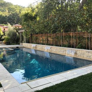 Foto de piscina con fuente alargada, moderna, grande, rectangular, en patio trasero, con adoquines de piedra natural