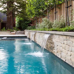 Ejemplo de piscina con fuente alargada, moderna, grande, rectangular, en patio trasero, con suelo de hormigón estampado