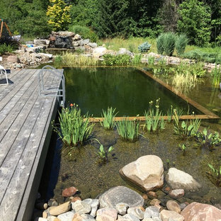 Small country backyard custom-shaped natural pool in Toronto with decking.
