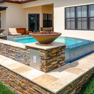 Example of a small minimalist backyard stone and custom-shaped aboveground hot tub design in Miami