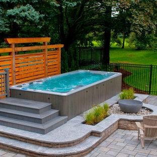 Immagine di una piscina di medie dimensioni e dietro casa con fontane e pedane