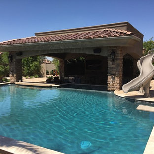 Large transitional backyard rectangular lap pool in Phoenix with a water slide and natural stone pavers.