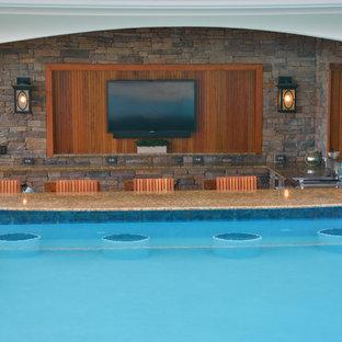 Modelo de casa de la piscina y piscina de tamaño medio, a medida, en patio trasero, con adoquines de hormigón
