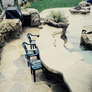 Ejemplo de piscina con tobogán tropical, a medida, en patio trasero, con suelo de hormigón estampado