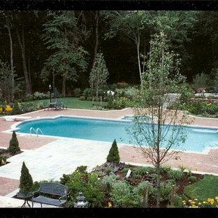 Large elegant backyard brick and custom-shaped pool photo in New York