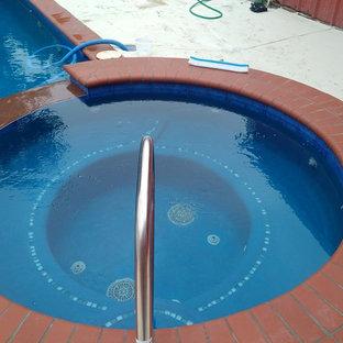 Ejemplo de piscinas y jacuzzis alargados, campestres, de tamaño medio, rectangulares, en patio trasero, con losas de hormigón