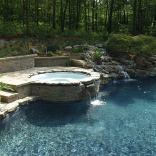 Photo of a traditional swimming pool in New York with a hot tub.