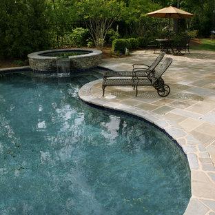 Ispirazione per una grande piscina contemporanea personalizzata dietro casa con pavimentazioni in pietra naturale e una vasca idromassaggio