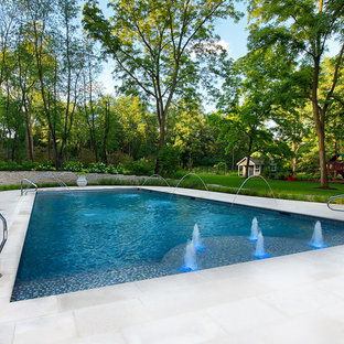 Design ideas for a large traditional backyard rectangular lap pool in Chicago with a water feature and tile.