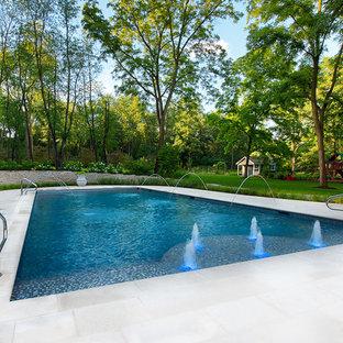 Diseño de piscina con fuente alargada, tradicional, grande, rectangular, en patio trasero, con suelo de baldosas