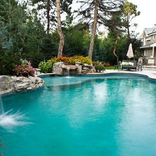 Imagen de piscina con fuente natural, rústica, grande, a medida, en patio trasero, con adoquines de hormigón