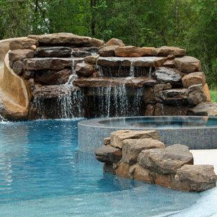 Стильный дизайн: большой бассейн произвольной формы на заднем дворе в стиле рустика с водной горкой и покрытием из каменной брусчатки - последний тренд