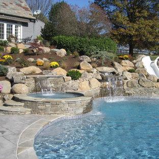 Imagen de piscina con tobogán natural, actual, grande, a medida, en patio trasero, con adoquines de hormigón
