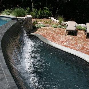 Modelo de piscina con fuente infinita, tradicional, grande, a medida, en patio trasero, con adoquines de ladrillo