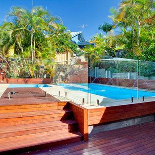 Immagine di una piscina stile marinaro rettangolare di medie dimensioni e dietro casa con fontane e pedane