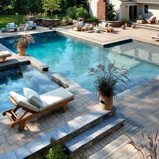 Modelo de piscinas y jacuzzis alargados, tradicionales, grandes, a medida, en patio trasero, con adoquines de piedra natural