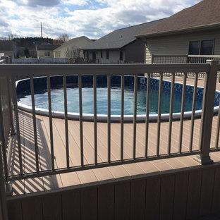 Imagen de piscina tradicional, de tamaño medio, redondeada, en patio trasero, con entablado