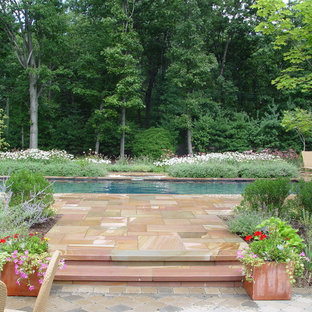 Photo of a large mediterranean back rectangular lengths swimming pool in New York with a water feature and natural stone paving.