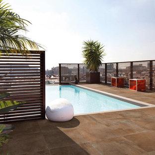 Diseño de piscina alargada, actual, de tamaño medio, rectangular, en azotea, con suelo de baldosas