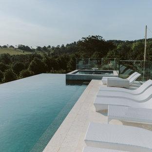 Exemple d'une piscine sur toit hors-sol tendance de taille moyenne et rectangle avec un bain bouillonnant et des pavés en pierre naturelle.