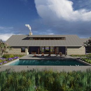 Diseño de piscina de estilo americano, de tamaño medio, rectangular, en patio delantero, con losas de hormigón