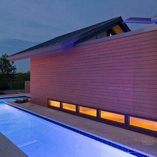 Cette image montre une très grand piscine design sur mesure avec une cour.