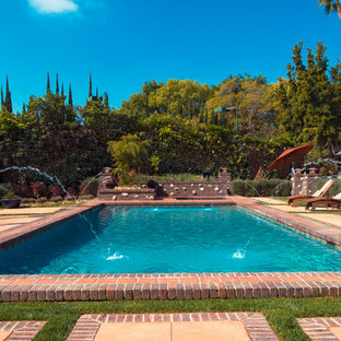 This is an example of a large country backyard rectangular lap pool in Los Angeles with brick pavers and a water feature.